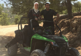 Rahhal and her fiancé ride smile while on an ATV during a trip to Jordan in the Middle East.