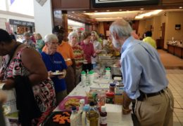 """Tom Keyserling (right), the principal investigator for the lifestyle study within the Heart Healthy Lenoir project, serves up heart-healthy fare at the """"Living the Good Life Expo"""" in Vernon Park Mall in Kinston, North Carolina."""