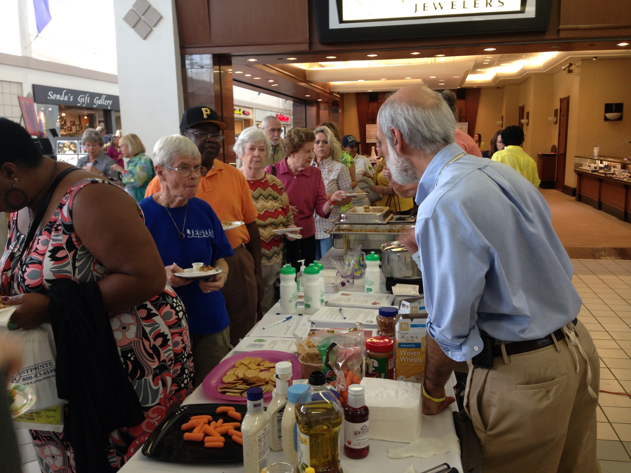 "Tom Keyserling (right), the principal investigator for the lifestyle study within the Heart Healthy Lenoir project, serves up heart-healthy fare at the ""Living the Good Life Expo"" in Vernon Park Mall in Kinston, North Carolina."
