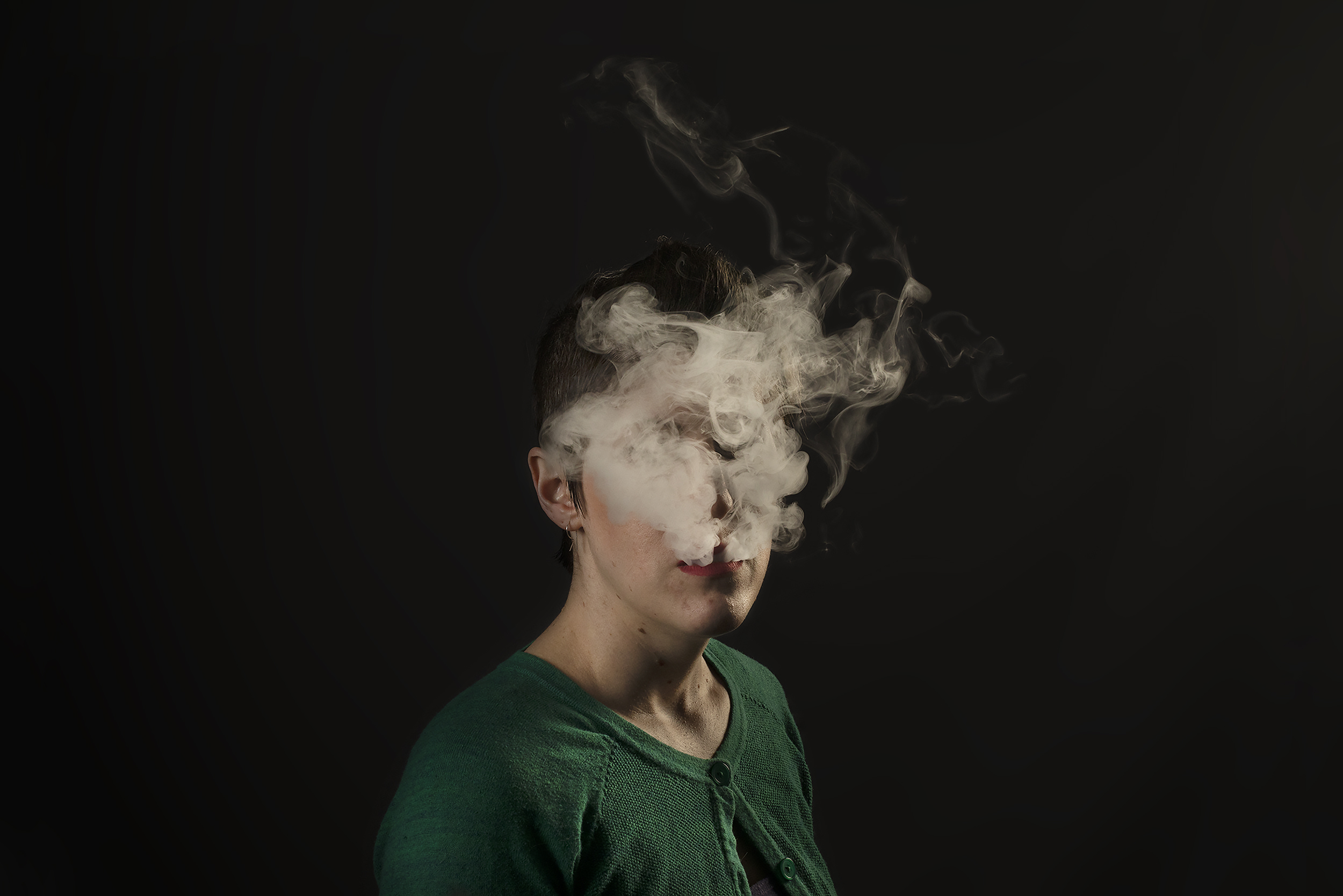 a puff of vapor covers a young woman's face
