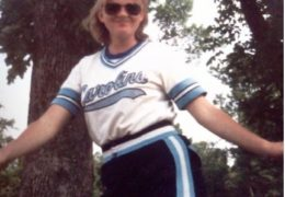Susan Wilson smiles at the camera in a picture from the early 1980s of her in her Carolina softball jersey