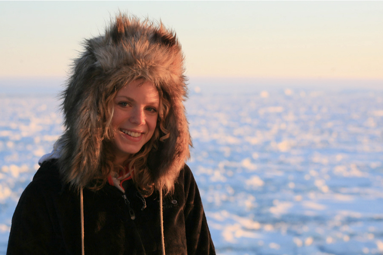 Zena Cardman poses in a thick winter coat and hat while conducting research on the West Antarctic Peninsula.