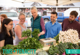 Alice Ammerman looks at cilantro along with four other people at the Carrboro Farmers' Market