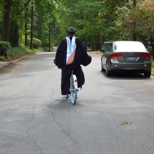 Alice Ammerman in cap and gown riding a Carolina blue bike down the street