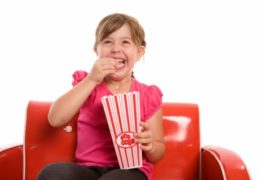 Little girl sits in chair with a box of popcorn, smiling