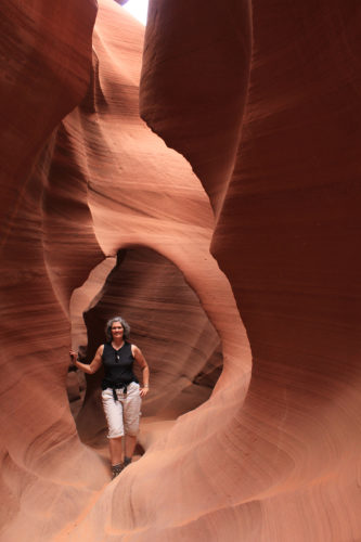 a woman leans against a red canyon wall in Arizona