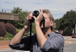 John Bechtold holds a camera and shoots up