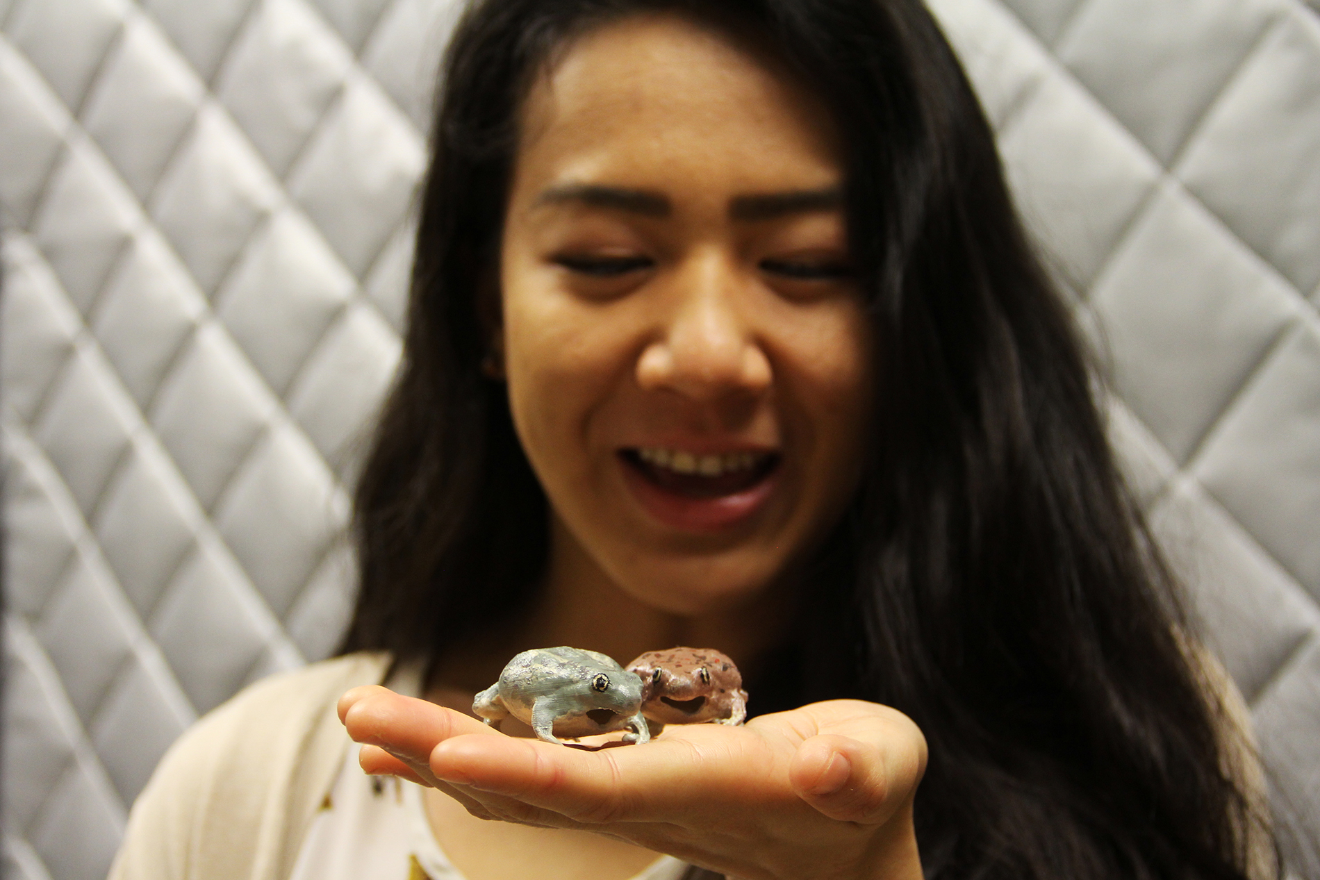 a female researcher holds two 3-D printed spadefoot toads