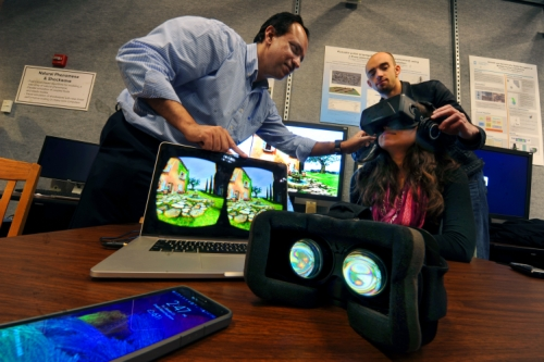 Dinesh Manocha and Carl Schissler, a UNC graduate student in computer science, assist the author with the headphones and virtual reality headset.
