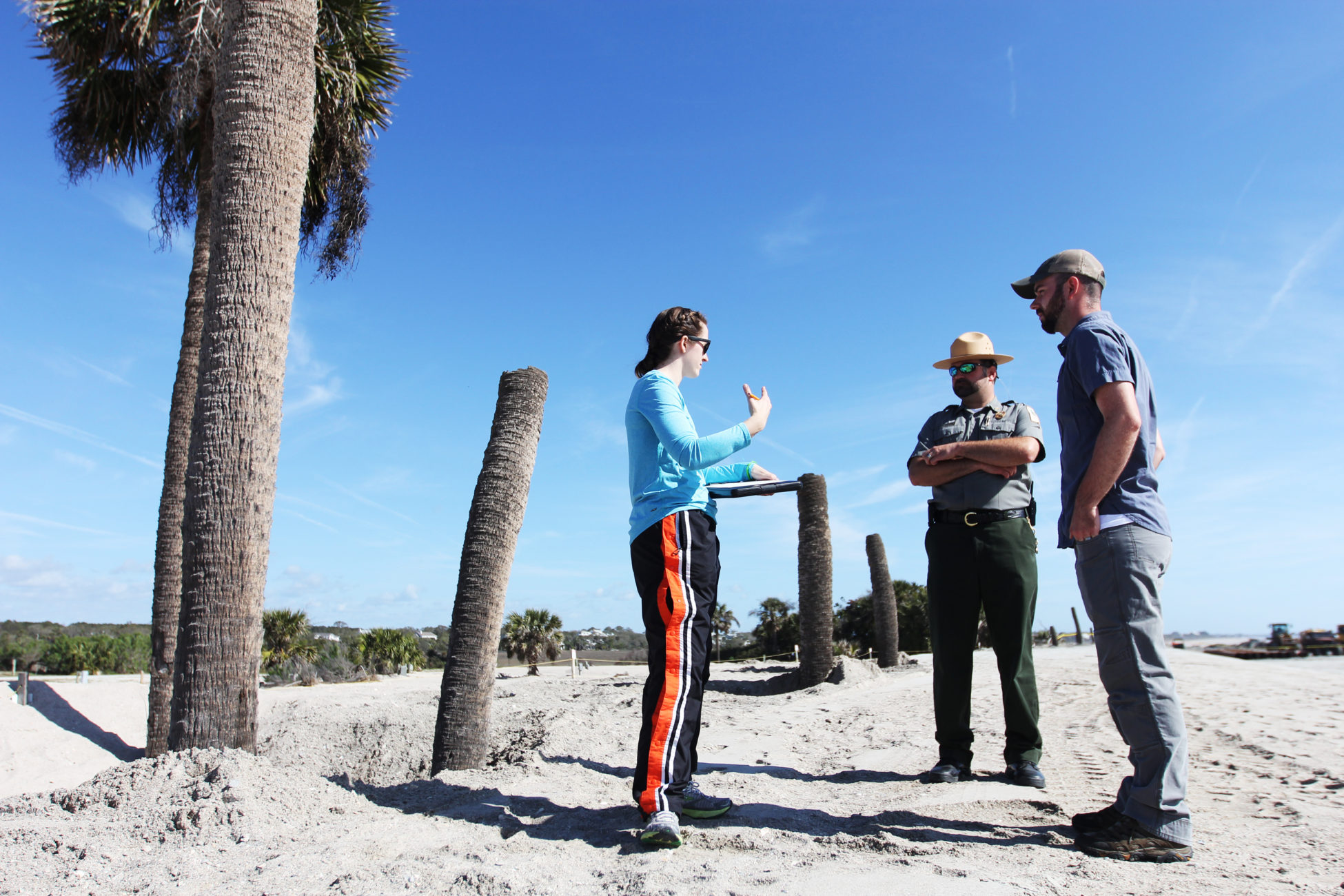 Elsemarie deVries and Joe Lemeris talk to an officer on the beach about their research
