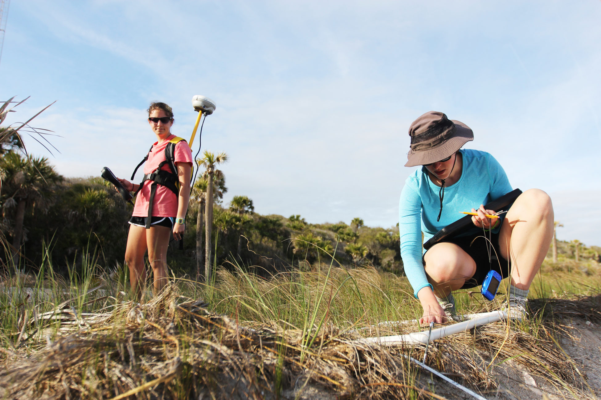 Elsemarie deVries measures the vegetation along her last transect while Atencio gathers the GPS points of each quadrat