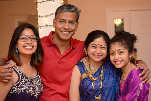 a young Indian family smiles for a photo