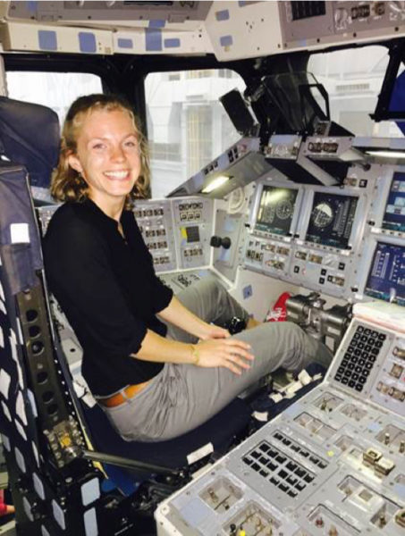 Cardman poses while sitting in a pilots seat in the flight deck of a shuttle simulator.