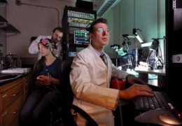 Photo of Flavio Frohlich looking at him computer as graduate student Michael Boyle attaches a head piece to graduate student Kristin Sellers.