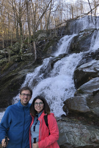 Eleftheria Kontou and her spouse in front of a waterfall