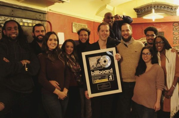 Alex Kresovich (center) with friends and family as he holds a billboard #1 recognition plaque