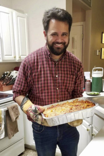 Ben Frey holds a pan of lasagna in a kitchen