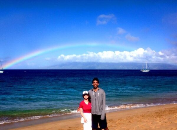 Aaron Anselmo and his wife on a beach with a rainbow behind them