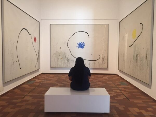 Margarett McBride sits in front of a piece of art at a gallery