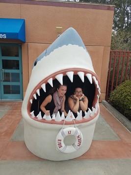 Stephanie Smith and friend pose inside a set of plastic shark jaws