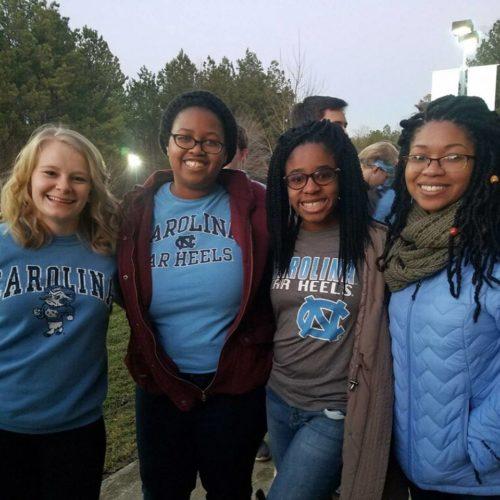 four 20-something girls donning Carolina blue/UNC shirts