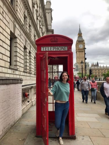 a young girl stands in front of a an iconic red telephone box in London - Big Ben stands tall in the background