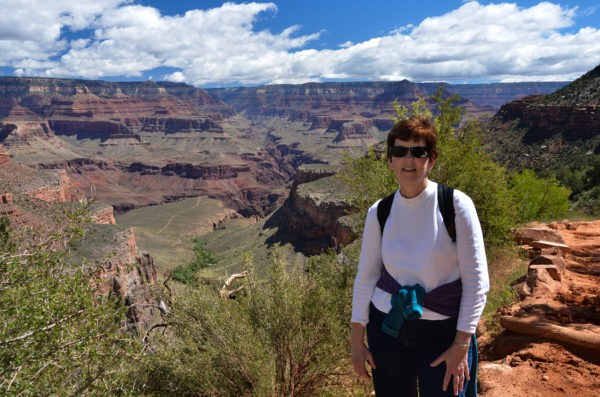 a woman in sunglasses and hiking clothes stands tall with the Grand Canyon behind her