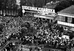 "A large crowd of people gather in front of a sign that reads ""Stoczni Gdańskiej im. Lenina."""