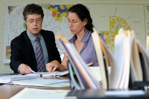 Photo of Gabriel Cummings and Heather Hunt looking of paper and discussing.