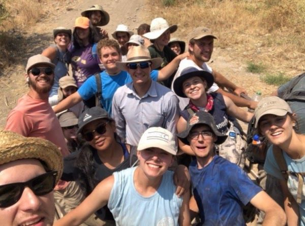 Chloe Scattergood and a group of students at a dig site