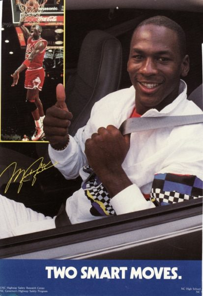 "Michael Jordan sitting in a car, wearing his seat belt, giving a thumbs-up. Another image in the add shows Jordan playing basketball, and dunking the ball. Ad says ""Two smart moves"""