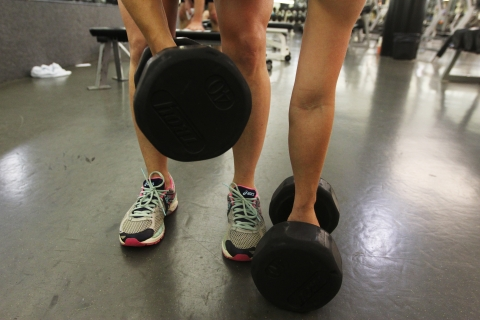 Showing one someones legs and feet, they stoop down to pick up two 40 pound hand weights