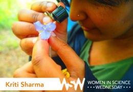 Kriti Sharma examines a purple flower with a magnifying glass