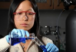 Photo of a female UNC researcher working with test tubes in the lab.
