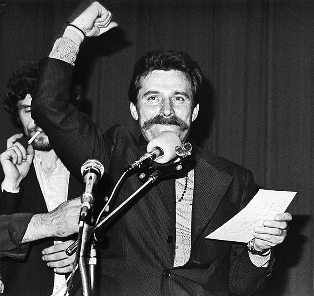 In this black-and-white photograph, a mustachioed man stands before a microphone, holding a sheet of paper in his left hand and raising his right hand in the air.