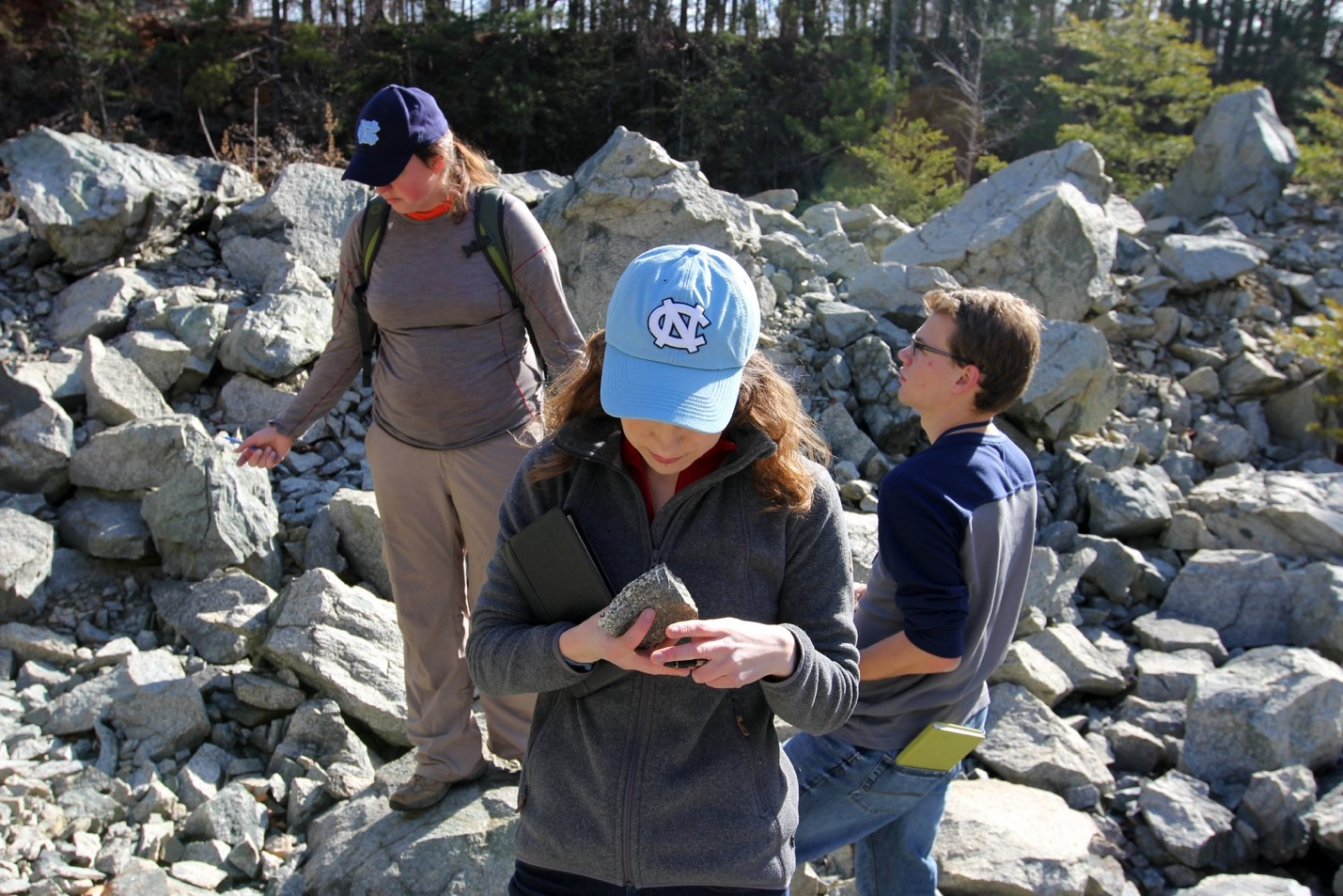 a girl with observes a rock closely