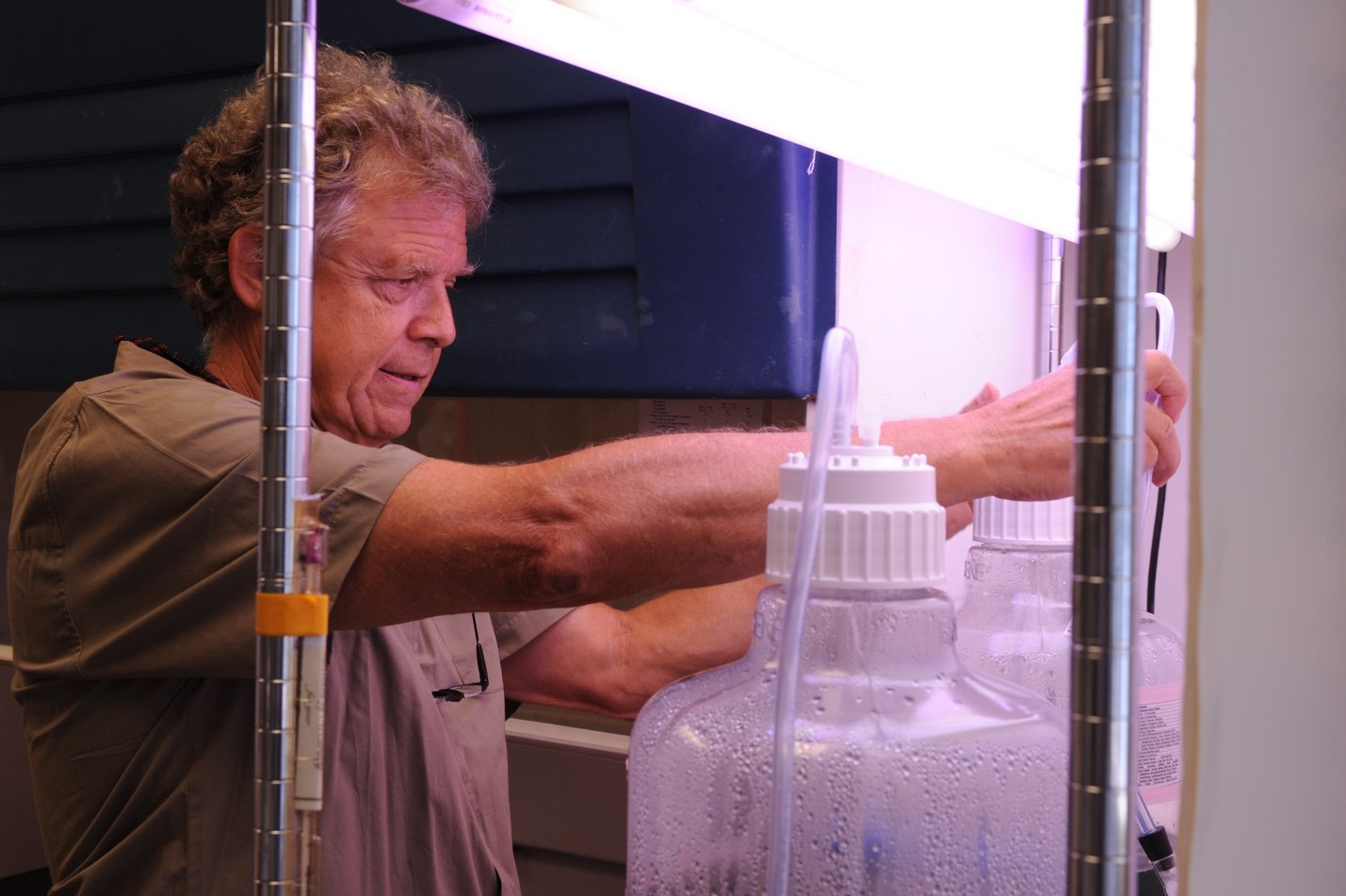 a man examines water samples in big plastic containers