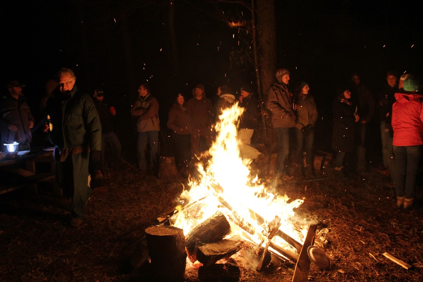 people stand around a bonfire