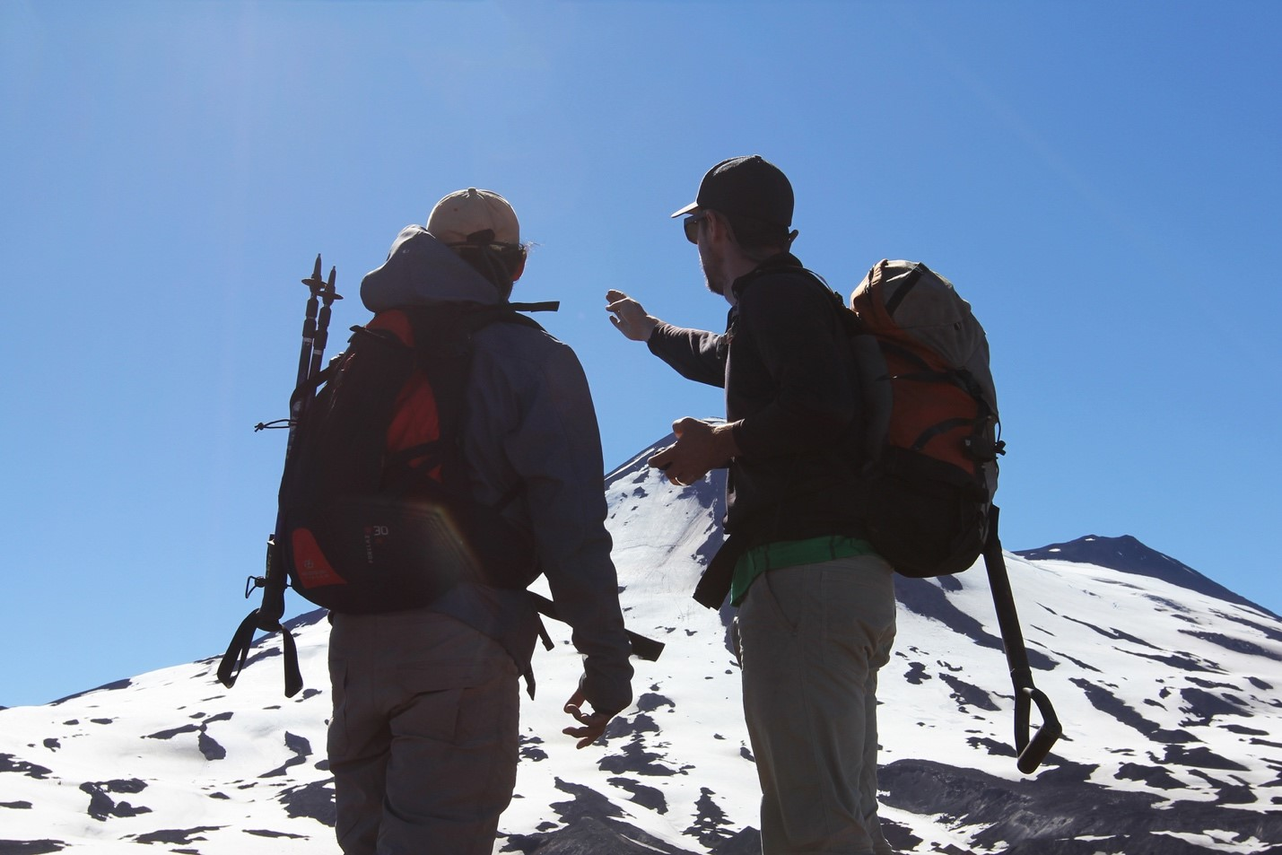 two men wearing hiking backs look up at an active volcano