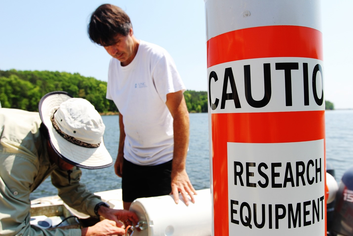 two men prepare equipment before lowering it into the lake to run tests