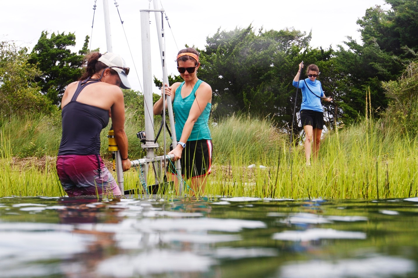 three girls guide a fish-finding rig into a marsh