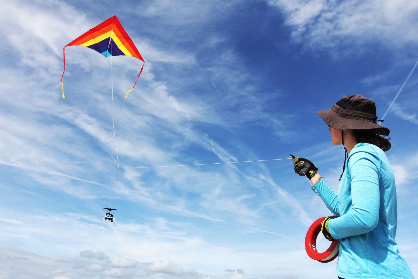 a girl uses a kite to get arial footage of a beach