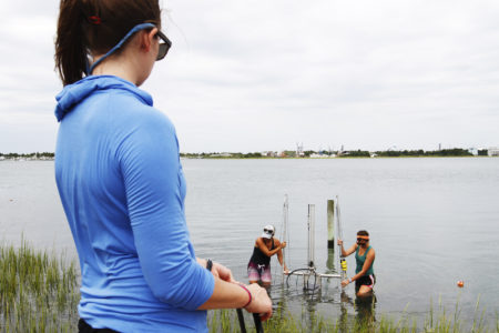 One girls looks on as two other girls carry a rig out of the lake.