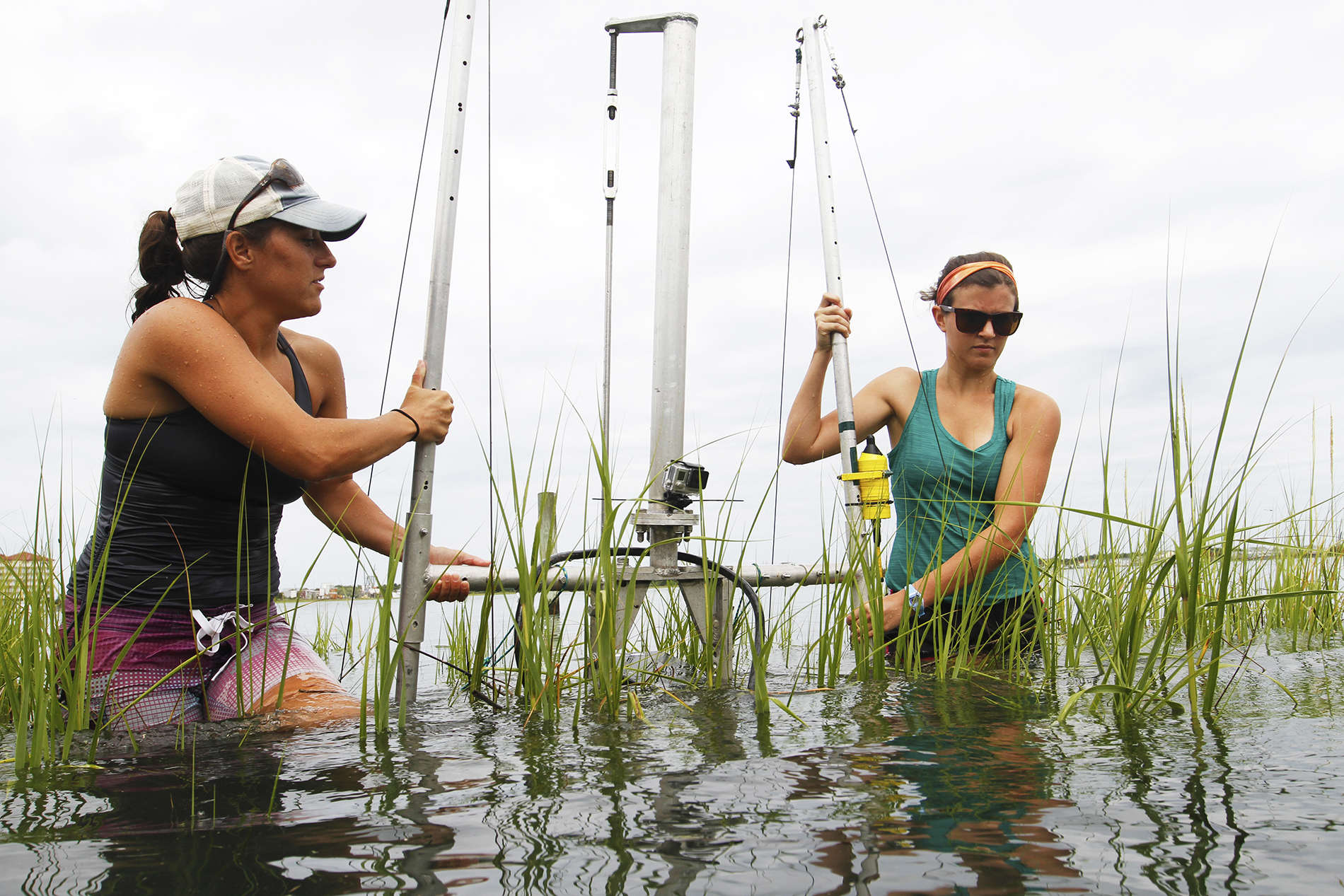 two girls place a sonar rig in a lake