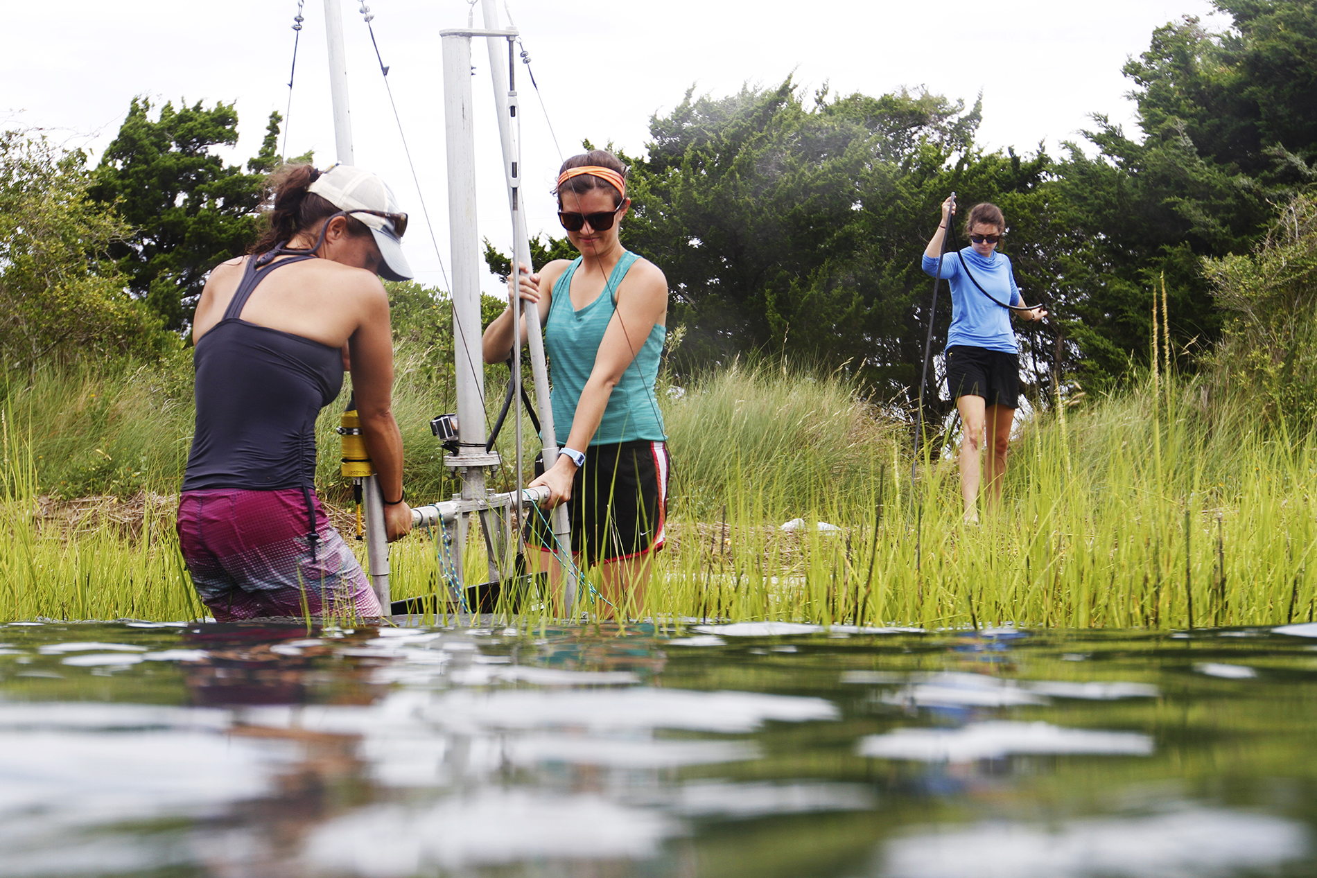 two girls move a rig into a lake, while a third follows with a battery pack