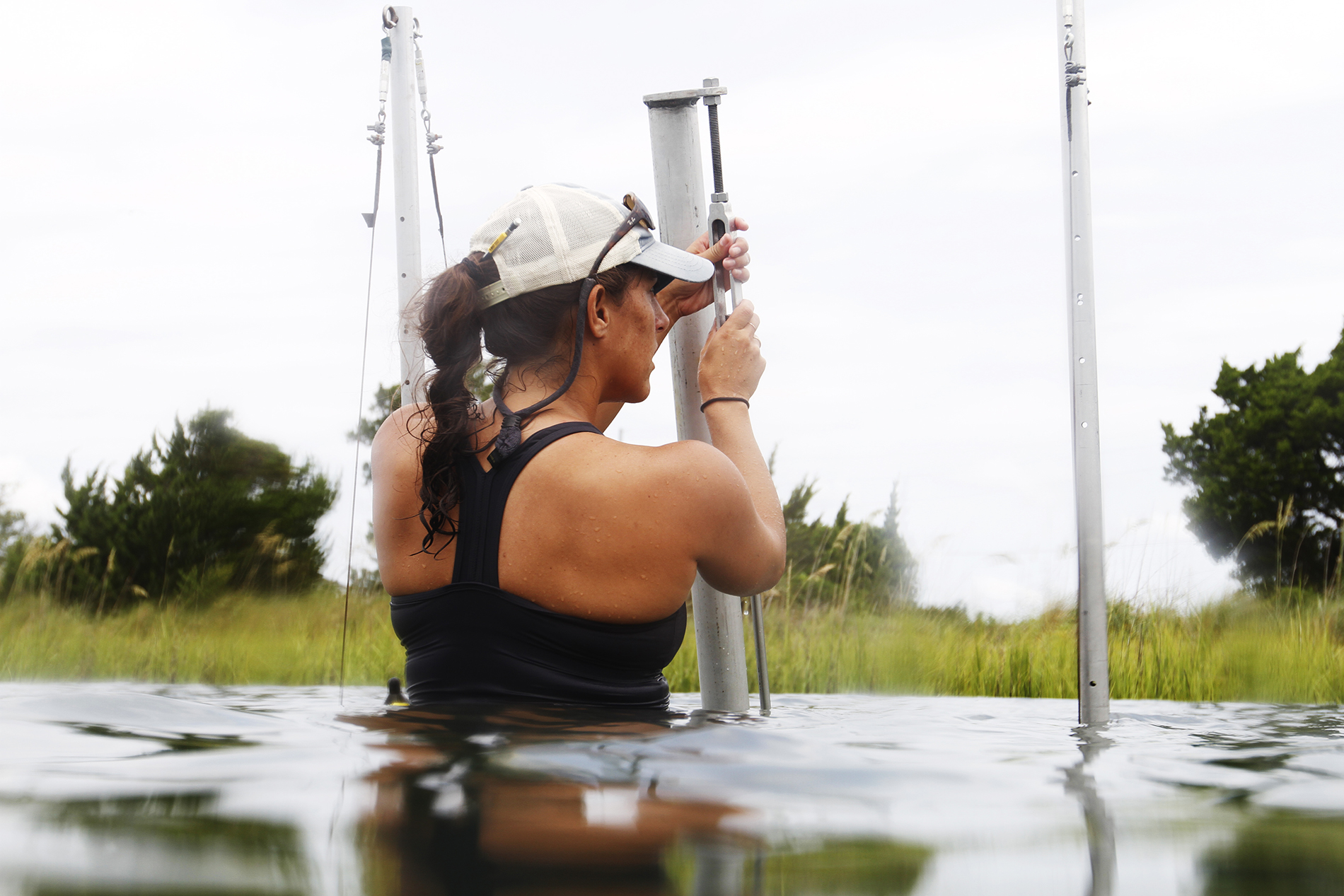 a girl adjusts a camera rig in the lake