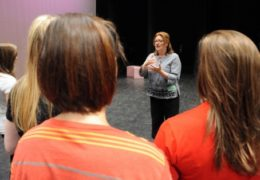 Photo of Heather Patterson King talking to students during a PlayMakers outreach program.