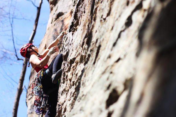 woman climbs rock wall