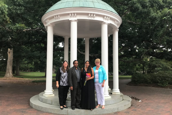 A UNC classic: Ramdeen (second from right) stands with her family at the Old Well after successfully defending her dissertation on July 28.