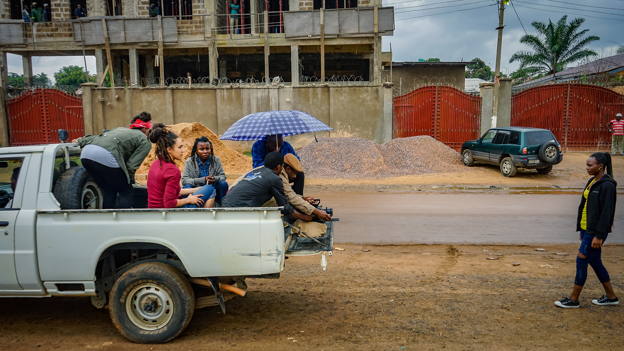 Ndaliko and a film team sit in the back of a white pickup truck and film a girl walking toward the truck's cab